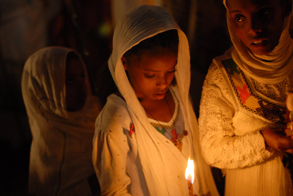 ADDIS ABABA, ETHIOPIA.  Three young girls hold candles during a visit by the Ethiopian patriarch at Holy Trinity Church, where former Emperor Halle Selassie is buried, during the Coptic millennium on September 11, 2007. Ethiopia's Coptic calendar means Ethiopia celebrates the millennium seven year later than the rest of the world on September 11.