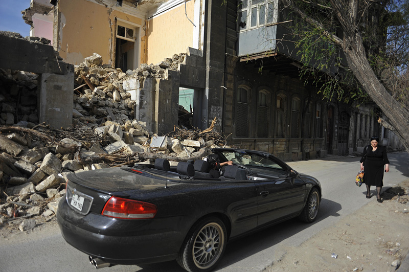 BAKU, AZERBAIJAN.  A man drives by in a convertible as a woman walks down the street beside a demolition site where a parking garage, park, and tunnel are planned after the government forced the eviction of several residents over several blocks to make way for the new project in the Besh Mertebe neighborhood on April 12, 2012.
