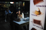 SARAJEVO, BOSNIA AND HERZEGOVINA.  Friends share a moment looking at cell phone pictures in front of a dessert shop in the old city on October 11, 2014.