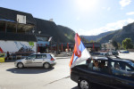 VISEGRAD, REPUBLIKA SRPSKA, BOSNIA AND HERZEGOVINA.  A man waves a Serbian flag as part of a wedding procession through the streets on October 18, 2014.  Visegrad was ethnically cleansed by the Bosnian Serb Army during the 1992-1995 conflict; a plaque on the statue beside the café in the background states, {quote}Monument to defenders of the Republika Srpska from the grateful people of Visegrad{quote}.