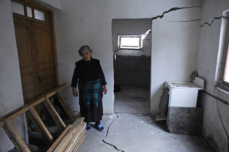 DGVARI, GEORGIA.  Zhenia Gogoladze, 68, outside her house which has been partially destroyed by cracks appearing after a 2007 earthquake in Dgvari, Samstkhe-Javakheti region, Georgia, one village over from Tadzrisi from where the Baku-Tbilisi-Ceyhan (BTC) oil pipeline crosses through the Caucuses mountains, on January 22, 2012.  Due to soft soil, many homes in Dgvari have cracked due to landslides and earthquakes and experts have asserted that the pipeline construction, which included controlled blasts, in the mountain villages near the city of Borjomi may have helped accelerate the pace of seismic activity in the region, although locals believe the pipeline construction are unconnected to recent earthquakes and landslides.