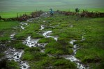 NEAR DEBRE BIRHAN, ETHIOPIA.  A woman rides her horse down a muddy trail during the wet season five kilometers southwest of Debre Birhan, Ethiopia on September 2, 2007. As Ethiopians in the capital Addis Ababa prepare for the Coptic millennium celebrations on September 11, 2007, life in the countryside continues with little fanfare.  (Credit: Amanda Rivkin/Associated Press)