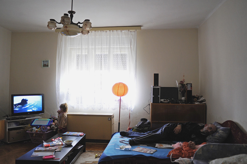 AJKA TOSOKBEREND, HUNGARY.  Dora Jazmin Juhasz, 3, watches television as her father, Zoltan Juhasz, 33, sleeps in their temporary home on November 23, 2010; Dora's fourteen month old younger sister, Angyalka, was the youngest victim of an industrial accident at the MAL plant in nearby Ajka, Hungary on October 4, 2010 which sent a torrent of toxic red alumina sludge gushing through their previous home in Devecser, Hungary.  Zoltan has burns that cover 67% of his body due to the accident and despite nearly drowning in the sludge save for a single arm, Dora survived without injury.