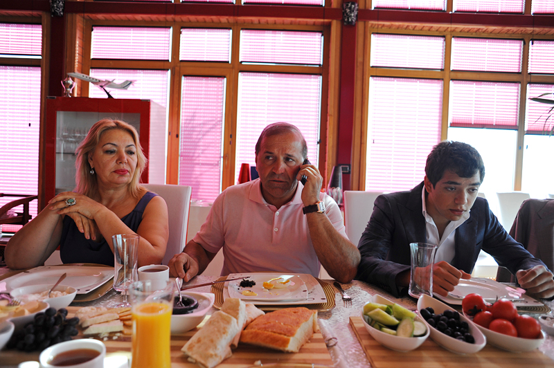 BAKU, AZERBAIJAN.  (Center) Ibrahim Ibrahimov, an Azerbaijani oligarch and billionaire, talks on his cell phone at the breakfast table while seated between his wife (at left) Valida Ibrahimli and son Huseyn, 18, in one of several houses on his Caspian seaside property he used to inhabit with his family in the Garadagh region just southwest of Baku, Azerbaijan on July 18, 2012. Ibrahimov is the developer behind the Khazar Islands artificial islands project; in his private life, he enjoys building a home for his family, moving in, and then quickly tires of the property before building a new home on an adjacent lot on his seaside lands.  (Credit: Amanda Rivkin/VII Mentor Program for The New York Times Magazine)