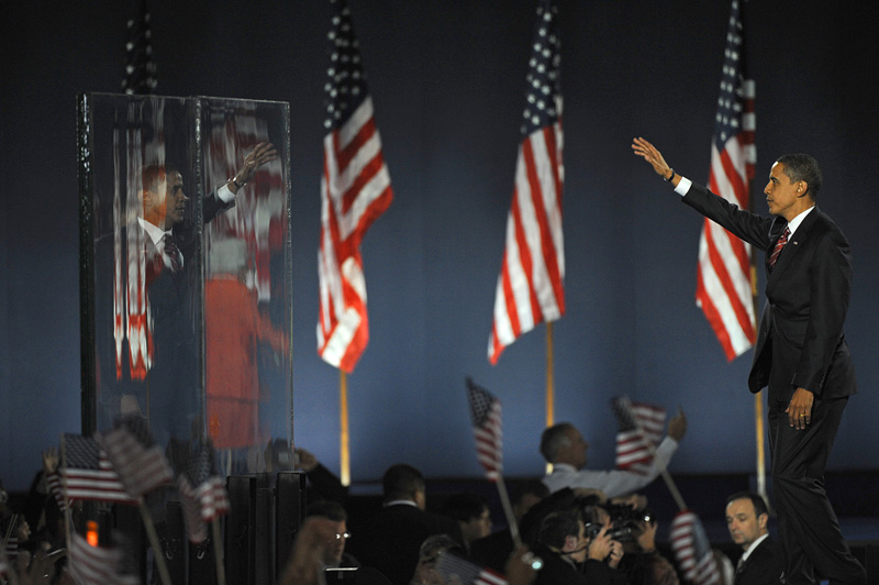 CHICAGO, ILLINOIS.  Democrat Barack Obama waves to his supporters in Grant Park, Chicago through bullet proof glass after winning the U.S. presidential election, defeating Republican John McCain, to become the 44th U.S. president on November 4, 2008.  Obama gave his victory speech to a crowd of just over 200,000 supporters.