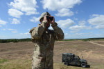 DRAWSKO POMORSKIE TRAINING AREA, POLAND.  Sergeant Stephen Murphy with the Fourth of the 319th Airborne Field Artillery Regiment of the 173rd Airborne Brigade Combat Team monitors an airdrop from a C-17 aircraft that took off from Nuremberg, Germany before it drops members of his unit on June 15, 2015.  NATO is engaged in a multilateral training exercise {quote}Saber Strike,{quote} the first time Poland has hosted such war games, involving the militaries of Canada, Denmark, Germany, Poland, and the United States.