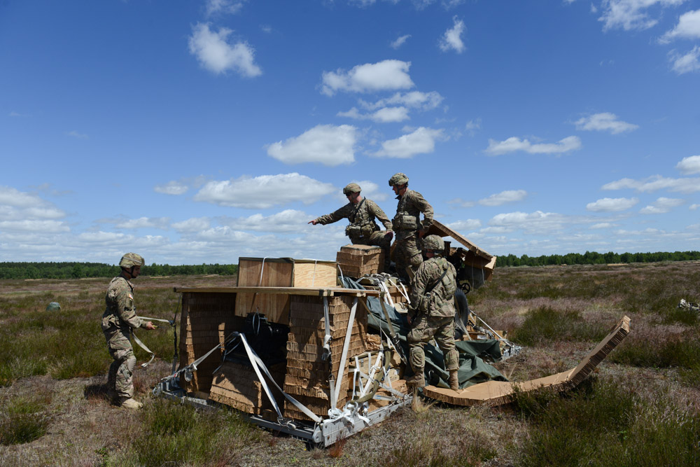 DRAWSKO POMORSKIE TRAINING AREA, POLAND.  American soldiers with the Fourth of the 319th Airborne Field Artillery Regiment of the 173rd Airborne Brigade Combat Team proceed to assemble a howitzer following an airdrop from a C-17 aircraft that took off from Nuremberg, Germany and dropped on June 15, 2015.  NATO is engaged in a multilateral training exercise {quote}Saber Strike,{quote} the first time Poland has hosted such war games, involving the militaries of Canada, Denmark, Germany, Poland, and the United States.