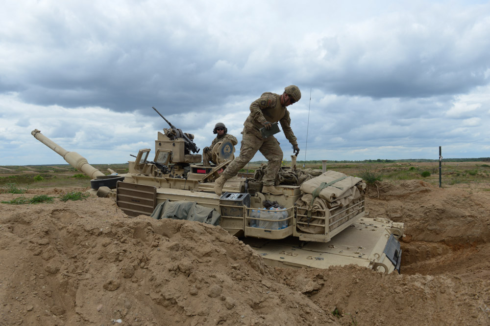 DRAWSKO POMORSKIE TRAINING AREA, POLAND.  American soldiers with the 2nd Battalion, 7th Infantry Regiment, 1st Armored Brigade Combat Team, 3rd Infantry Division based out of Fort Stewart, Georgia in an American Abrams M1A2 tank in position during a live fire exercise on June 16, 2015.  NATO is engaged in a multilateral training exercise {quote}Saber Strike,{quote} the first time Poland has hosted such war games, involving the militaries of Canada, Denmark, Germany, Poland, and the United States.