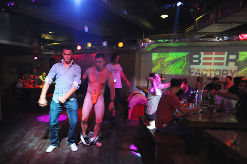 PRAGUE, CZECH REPUBLIC.  (L-r) Angelo Eleveld, 22, of Rotterdam, the Netherlands, a stag tourist celebrating the impending marriage of his friend (not pictured) Michael Klos, 23, dances with stranger and fellow stag tourist, the soon to be married Blair Skadden of New Zealand in the {quote}mankini{quote} made famous by British comedian Sasha Baron Cohen in the {quote}Borat{quote} film at the Beer Factory on Weneslaus Square in Prague, Czech Republic on August 12, 2011.