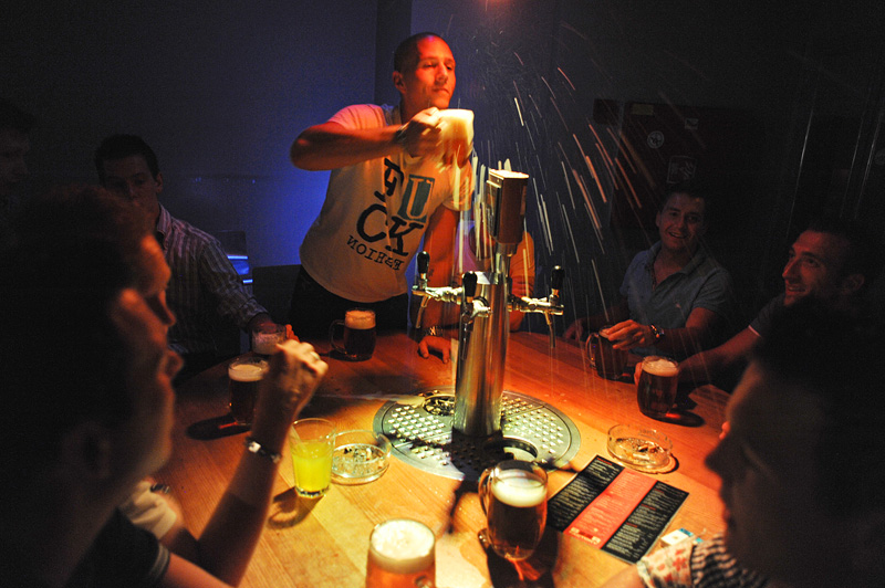 PRAGUE, CZECH REPUBLIC.  (Center) William Gerritsma, 23, of Rotterdam, the Netherlands, a stag night tourist, blows foam from the top of his beer at his friends at the Beer Factory on Weneslaus Square in Prague, Czech Republic on August 12, 2011.