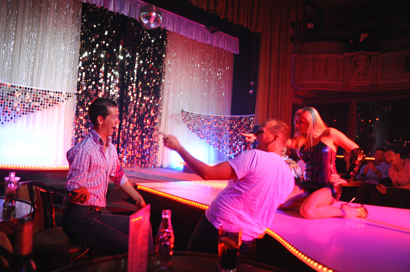PRAGUE, CZECH REPUBLIC.  (L-r) Stag night tourists Michael Klos, 23, whips his friend, Arnold Valkema, 27, of Rotterdam, the Netherlands with the aid of a stripper's prop and her encouragement at the Goldfinger strip club on Weneslaus Square in Prague, Czech Republic on August 12, 2011.