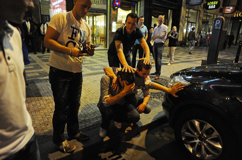 PRAGUE, CZECH REPUBLIC.  Stag night tourist Angelo Eleveld, 22, of Rotterdam, the Netherlands feels sick mid-way through the night as his friends alternatively seek to comfort and tease him while locals look on in consternation on Weneslaus Square in Prague, Czech Republic on August 12, 2011.  Michael Klos, 23, whose wedding a few weeks later was the occasion for the trip to Prague to celebrate his last nights of freedom, has his arm around his friend.