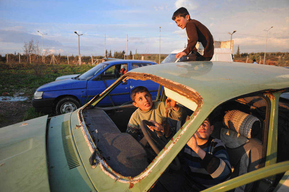 REYHANLI, TURKEY.  Syrian children play in a junkyard of old, abandoned and destroyed vehicles at the entrance to the Reyhanli tent city on February 26, 2012.  As the year old rebellion against the rule of Bashar Al-Assad continues just across the border in Syria, Turkey has seen a continued influx of refugees from the Syrian conflict but has not granted them refugee status and instead considers them to be {quote}guests{quote} of Turkey, the sign of another conflict fissure located precariously close to the pipeline route.