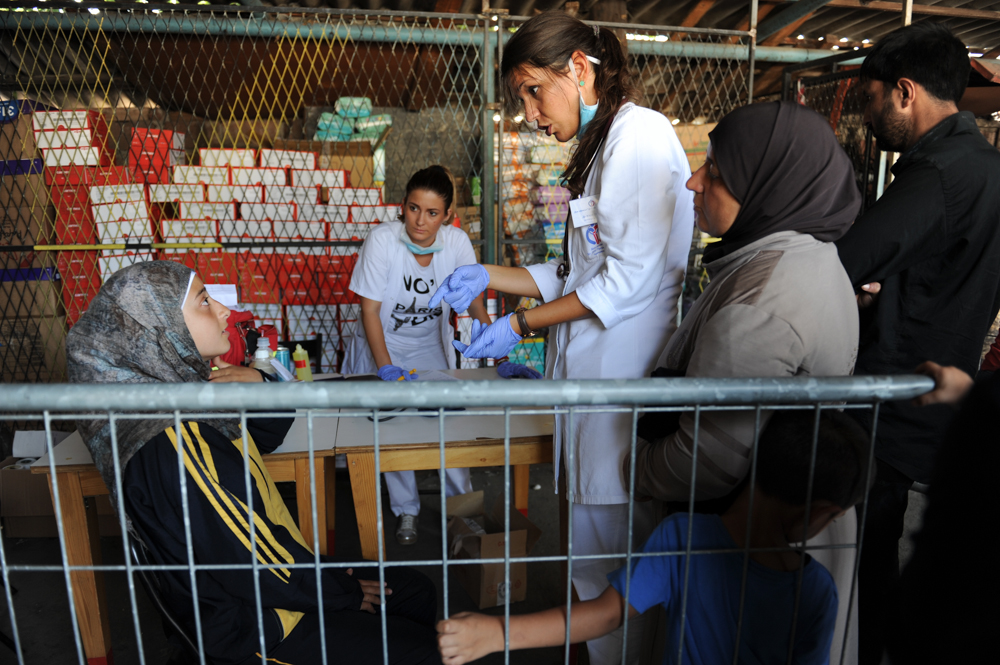 BELGRADE, SERBIA.  (L-r) Serbian nurse Ana Mitrovic and doctor Maja Grubac examine a girl from Syria at the Refugee Aid Serbia distribution center on September 3, 2015.  Thousands of refugees mainly from Syria but also Iraq, Iran and Afghanistan have made the journey from Turkey to Greece and through Macedonia before arriving in Serbia on their way to Europe in search of a better life, mainly in Germany.