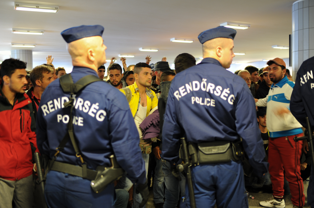 BUDAPEST, HUNGARY.  Police block the front of the line as refugees wait to board trains to Vienna before embarking onward to Germany, Switzerland and Sweden in the Keleti Train Station lower level on September 12, 2015.  Hungarian officials have struggled to control the flow of refugees through their country, building a wall at its borders, multiple refugee camps and ultimately attempting to prevent stampedes to board trains by those who made it all the way to Keleti Station in Budapest and the nationalist Prime Minister Viktor Orban has faced tremendous international criticism but no public condemnation in the process for his words and deeds.
