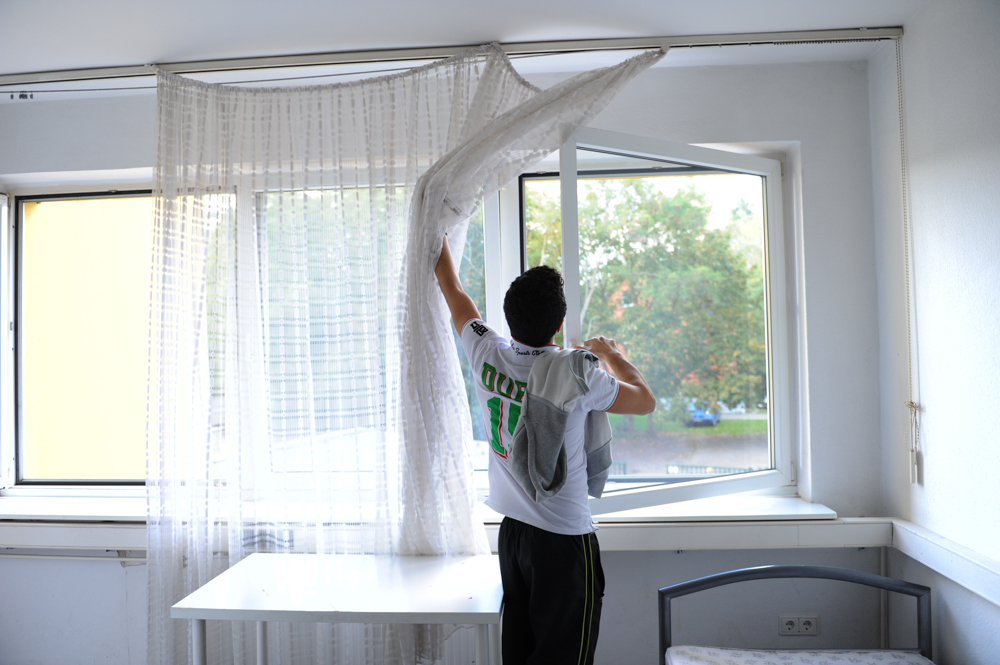 BERLIN, GERMANY.  Helmy opens the curtains to air out the smell of stale cigarette smoke in his mother Inayat's new room at a Gierso operated refugee dormitory in the outer ring of Berlin on September 24, 2015.  The family are Palestinians from Yarmouk, Syria and originally Haifa.