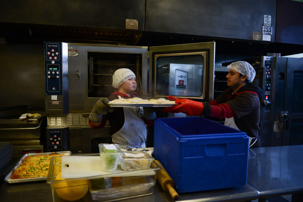 CHICAGO, ILLINOIS.  Employees of Gourmet Gorilla pull baked chicken from an oven in the kitchen in the West Town neighborhood on February 12, 2015.