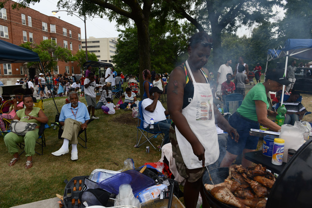 CHICAGO, ILLINOIS.  Melody Miller of St. Paul, Minnesota cooks jerk chicken and turkey legs over the grill during the back-to-school Bud Biliken Day Parade and Picnic, an annual tradition on the South Side, in Washington Park on August 9, 2015.