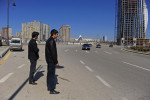 BAKU, AZERBAIJAN.  Cousin Hicran Aliyev, 21, and Asiman Tagili, 20, cross a major road to do the family's grocery shopping on the first day of the Novruz holiday celebrating the Zoroastrian new year on March 20, 2012.
