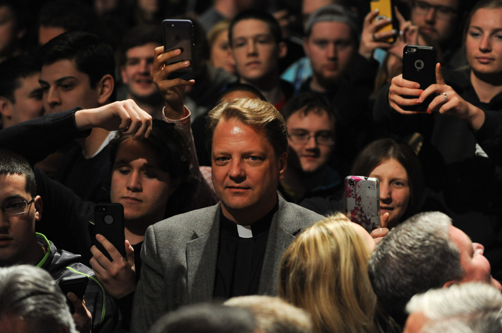 DE PERE, WISCONSIN.  A priest stands among students as Republican presidential frontrunner Donald Trump signs autographs and does what is known as {quote}a rope line{quote} in the Webster Theater at St. Norbert College after he gave a speech primarily on the topic of success not his presidential campaign on March 30, 2016.