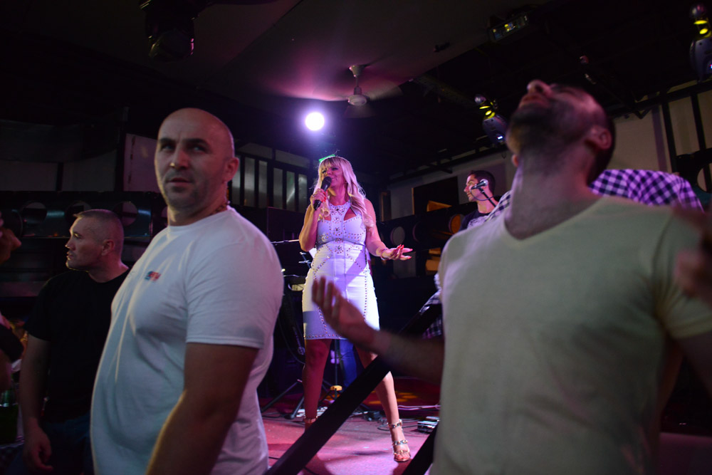 BELGRADE, SERBIA.  Dara Bubamara performs onstage at Bard, a nightclub on a splav or barge on the Danube River, surrounded by bodyguards on July 8, 2015.  Dara Bubamara's career extends back to 1989 when she got her start on television singing songs by Lepa Brena.