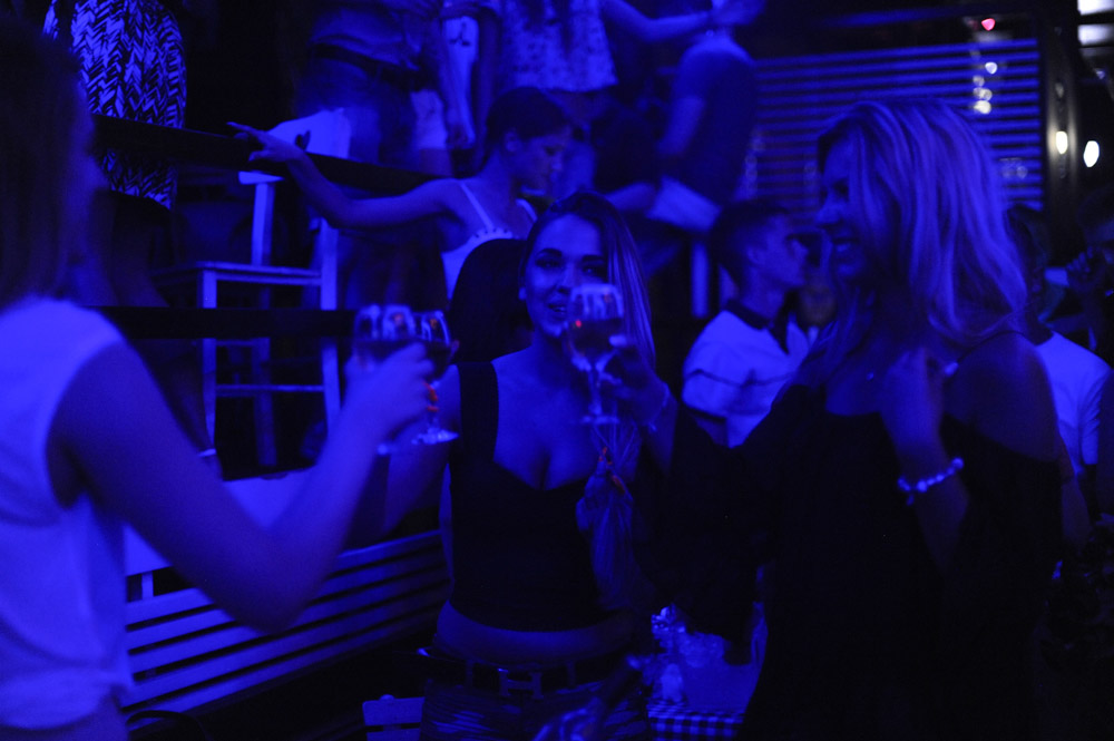 BELGRADE, SERBIA.  Clubgoers at Bard, a nightclub on a splav or barge on the Danube River, toast on the main dance floor of the club as Dara Bubamara sings fast-paced turbofolk hits on July 8, 2015.  Dara Bubamara's career extends back to 1989 when she got her start on television singing songs by Lepa Brena.