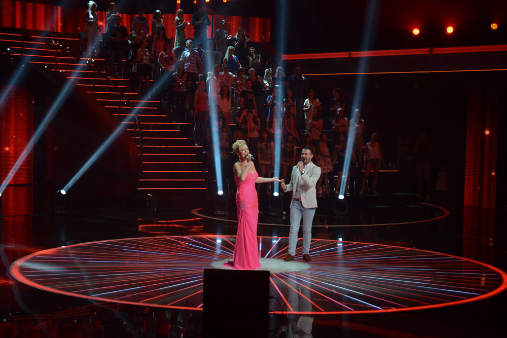 BELGRADE, SERBIA.  (At left) Lepa Brena, one of the oldest and original turbofolk stars, during a performance on the set of {quote}Zvezde Granda,{quote} or {quote}Grand Stars,{quote} a premier turbofolk showcase on Serbian television station TV Prva, on July 1, 2015.  During this particular taping of {quote}Grand Stars,{quote} well known stars are singing with younger, lesser known stars with the goal of elevating their personality in public life.