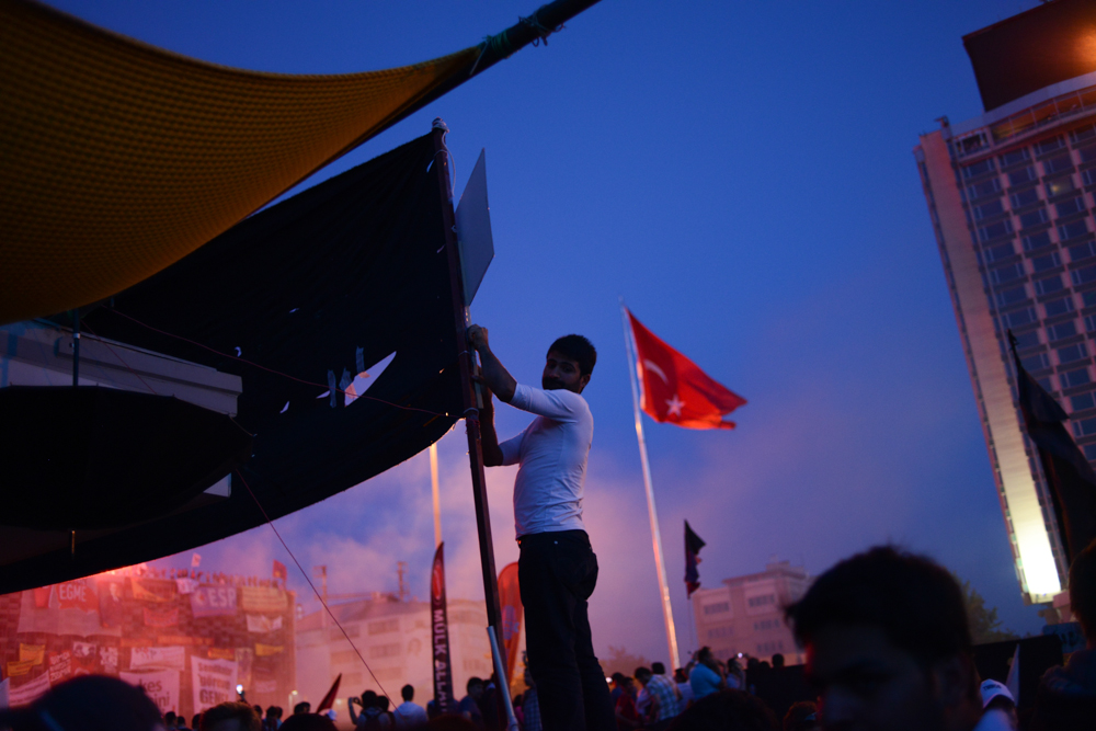 ISTANBUL, TURKEY.  The crowd in Taksim Square reacts to a pyrotechnics show of fireworks and torches in during ongoing protests against the Prime Minister Recep Tayyip Erdogan and his policies a week after demonstrators forced police to withdraw from the square have lead to a carnival-like sit-in on June 8, 2013. A week of protests led to police being barricaded out of and withdrawing from Istanbul's Taksim Square as it transforms increasingly into a free zone; the crisis, which began over construction of a park and plans to reconstruct Ottoman barracks and a shopping mall, has evolved into Turkey's biggest political crisis in decades as Turks express frustration with the current AK Party, Justice and Development Party and Prime Minister Recep Tayyip Erdogan.