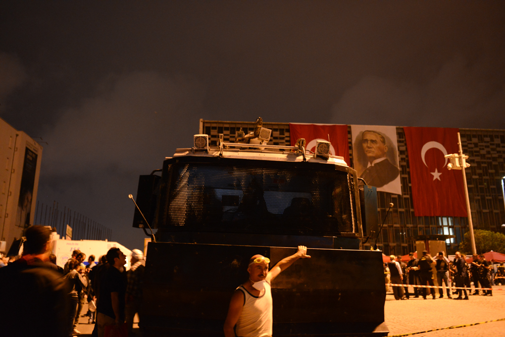 ISTANBUL, TURKEY.  A protester poses in front of a Turkish-made TOMA riot control vehicle in Taksim Square the evening after riot police moved to retake the square the night before on June 12, 2013. After 11 days of protest and occupying Gezi Park adjacent to Taksim Square, riot police firmly took control of Taksim Square with street battles on back streets occurring until the early hours of the morning and a few hundred demonstrators continuing to camp out in the adjacent Gezi Park.