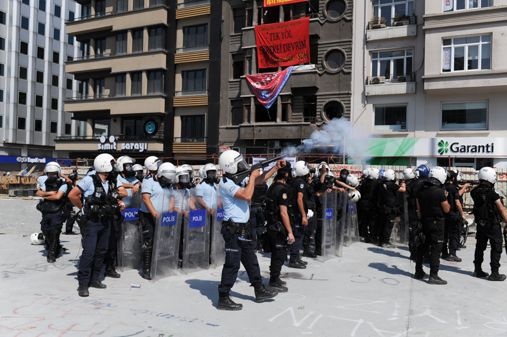 ISTANBUL, TURKEY.  Police fire tear gas at demonstrators on the road and into Gezi Park from Taksim Square as they move on the square on June 11, 2013. After 10 days of protest and occupying Gezi Park adjacent to Taksim Square, riot police moved to retake the square; last night, the Prime Minister called a meeting for tomorrow with protest leaders.