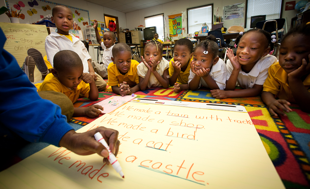 NWP_2010_Savannah1274.CR2 -- Chatham County (Savannah, GA) Board of Education Department Compensatory Program project director Pre-K LaWanda Ransom (wearing the red shawl, red and white striped shirt and black pants), works in a classroom with students at Spencer Elementary School Monday, May 3, 2010 in Savannah, Ga.  Photo by JASON E. MICZEK - www.miczekphoto.com