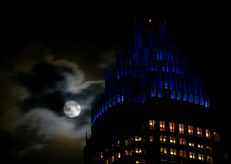The so-called Beaver Moon rises over the Bank of America high rise tower in uptown Charlotte.