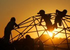 Children play on a playground jungle gym as the sun sets on the Optimist Club ballfields in Weddington, N.C.