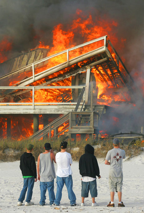 Five young men stare at a fully involved house fire at 22419 Front Beach Road from the beach side of the structure as firefighters from across Bay County fight the blaze.