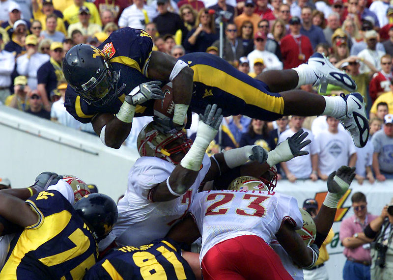 West Virginia's Kay-Jay Harris jumps over the Florida State defense to score a touchdown during the Toyota Gator Bowl in Jacksonville.