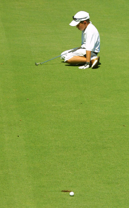 Christian Dolan, 10, of Augusta, Ga., falls to his knees after missing a par putt on hole nine on the Marshwood course.