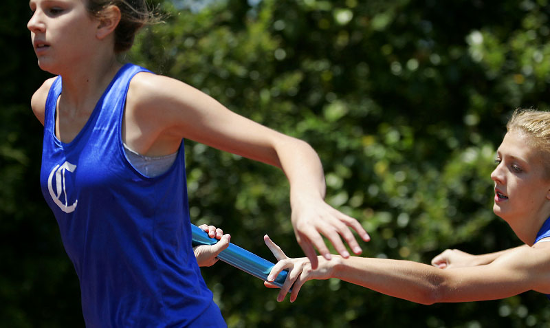 Charlotte Christian School's Alexa Dexter, right, a 14-year-old freshman, hands off a baton to fellow runner Jordan Todd, left, a 15-year-old freshman, during the girls 4 x 200 meter relay.