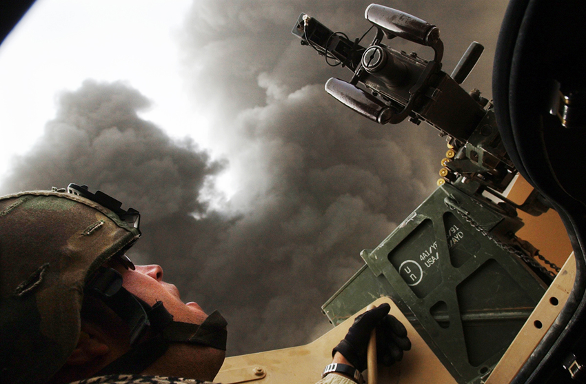Members of the RI Army National Guard's 173rd Long Range Surveillance Detachment patrol the area surrounding Forward Operating base Summerall near Baiji, Iraq. SPC Sean Judge, of looks up from the turret at a massive fire burns.