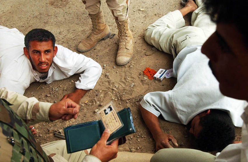 Interpreter Atheel Andrews a Christian Assryian from Chicago, left, with the RI National Guard's 119th Military Police Company, 1st Platoon, speaks with a group of Iraqi men whose vehicle was found to contained illegal munitions. The men were detained when their car was spotted on the side of the road; often the the case when insurgents plant I.E.D.s (improvised explosive devices).