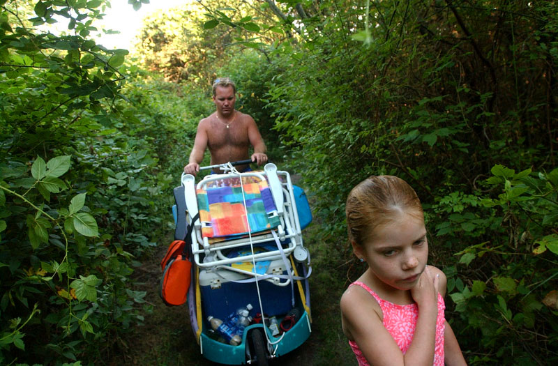 Following a day at the beach, eight-year-old Kate McElenny of New Jersey leads her dad, John McElenny, through a Clay Head trail with a collection of gear from their outing.