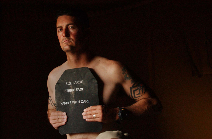 "Staff Sergeant Chet Crowell, 35, with the RI Army National Guard's 173rd Long Range Surveillance Detachment at forward operating base Summerall in Iraq, holds the ballistic plate from his ""flak jacket{quote} which must be worn by soldiers anytime the leave the base."