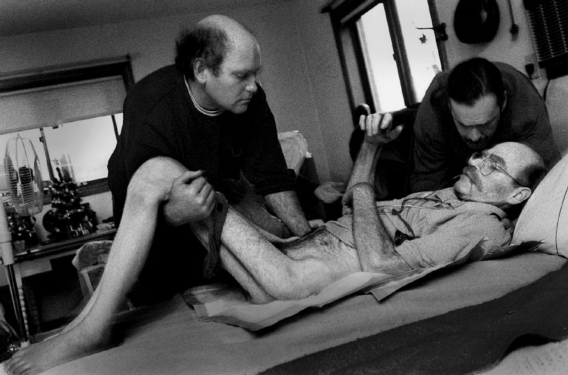 Earley's once-muscular legs reveal the ravages of his disease. His friends Bob Zuck, left, and Steven Ames, position him in his hospital bed, now moved in the living room.