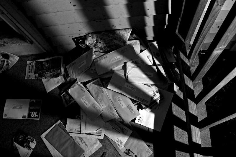 Legal documents, addressed to Jane and John Doe, pile up outside a rental property that the bank has repossessed. Lawyers for the bank are attempting to evict the tenants, who avoid collecting the mail. After numerous failed attempts to notify tenants, banks must go to court for eviction orders to force out the tenants.