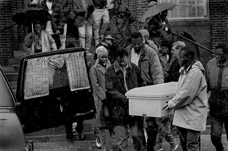 A rare April snow falls as pallbearers transport the body of Sunday Abek, 2, following a service in Manchester, NH. The young girl died of lead poisoning following exposure to leaded paint and lead-contaminated dust in and around the child's home according to the New Hampshire Dept. of Health and the CDC.