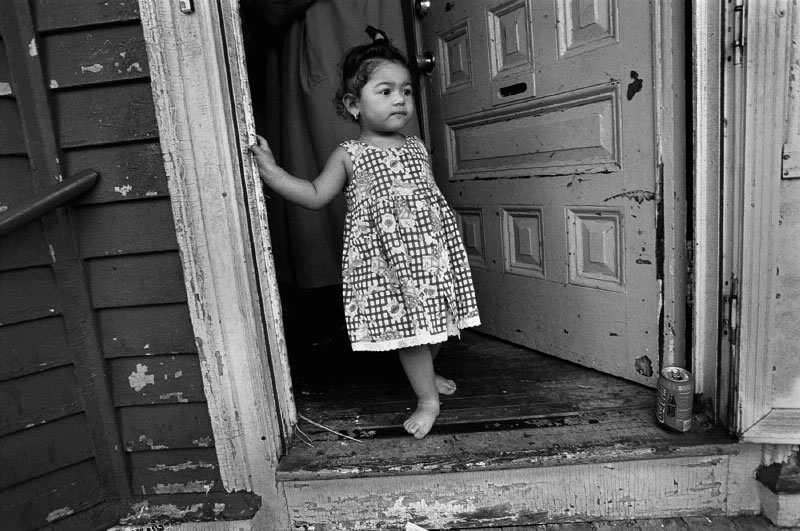 The fate of a young girl is unknown as she plays in the doorway of her triple-decker home. Her cousin, recently lead poisoned, is the third at this property since 1992. Non-compliance is historic at this property, which has also seen 31 code violations since 1984.