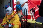 The whistle blows and performers gather at the backdoor trailer  for the start of another show. Outside the tent entrance Mike Snider, left, who graduated from the Ringling Brothers & Barnum Bailey's Clown College, Susan Vidbel granddaughter of the founding couple and Oleg Ryjkov of Russia wait for their cue.