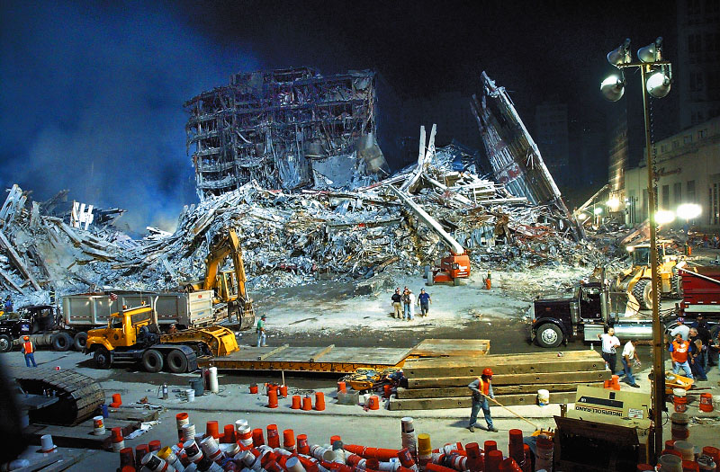 Following the 9/11 terrorist attacks on New York, emergency personnel work through the night to remove rubble along Liberty Street at the scene of the World Trade Center disaster.