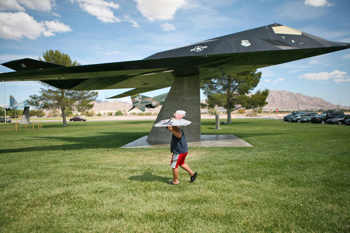 "Joshua Lopez, 7, carries a cardboard cutout of his grandfather Richard above his head while walking to a picnic in Freedom Park at Nellis Air Force Base Sunday, Aug. 12, 2007. The family, who refer to the cardboard cutout as ""Grandpa,"" take the cutout almost everywhere they go."
