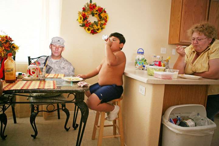 """Grandpa"" sits at the dinner table with Sprague's grandson Joshua Wednesday, Aug. 22 in North Las Vegas. Richard's wife Patt eats dinner at the counter nearby. The family always save a spot for the cutout when they eat dinner together."