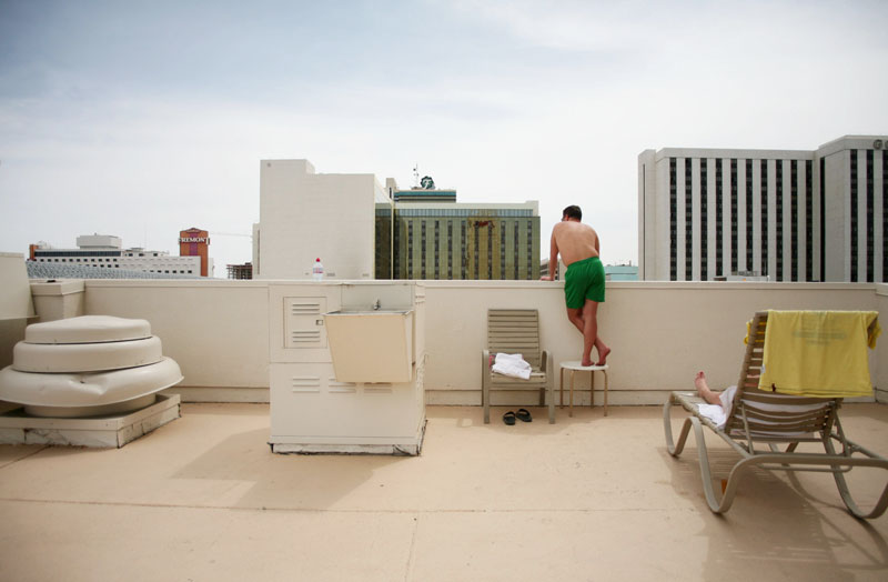 A sunbather takes a peak over the ledge of the 5th floor pool area to look down at the Vegas Grand Prix racetrack at the Plaza hotel-casino prior to the start of the race in Las Vegas, Nevada. Though other parts of the country experienced winter-like conditions, it was warm and sunny on race day in Las Vegas.